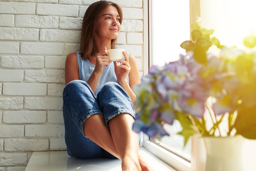 窓の外を見てお茶をしながら考える女性