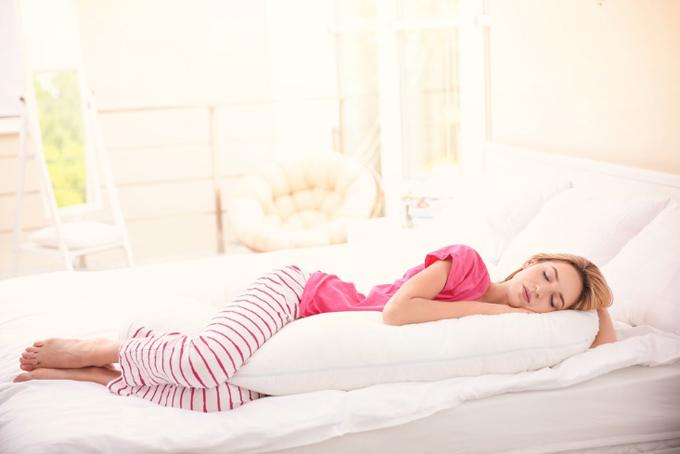 抱き枕で寝ている女性
