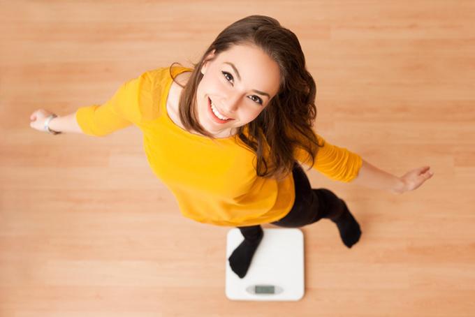 体重計に乗っている女性の画像