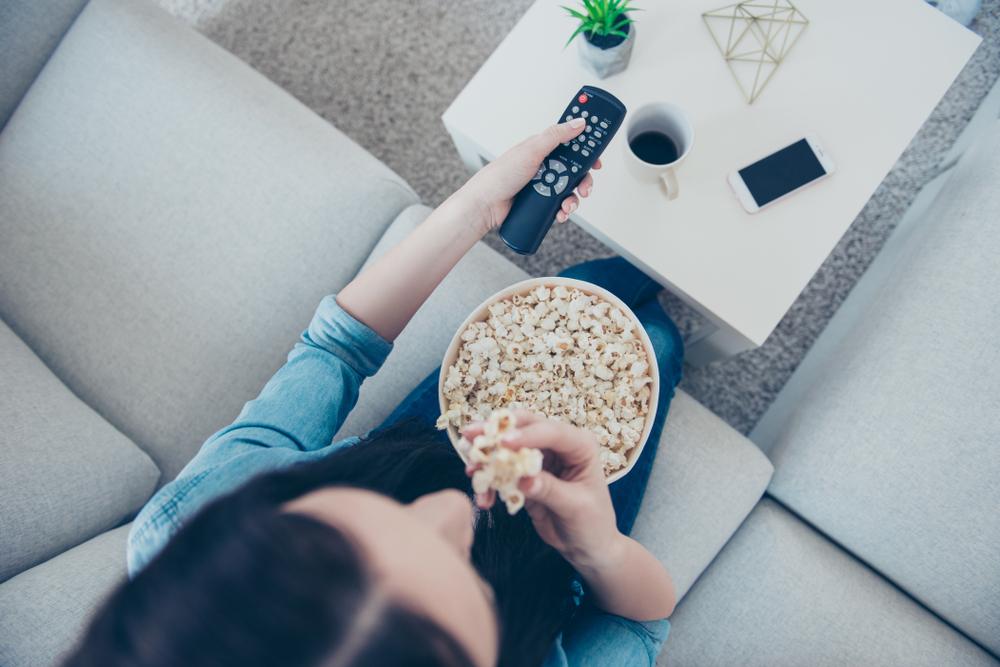 テレビみながらポップコーンを食べる女性