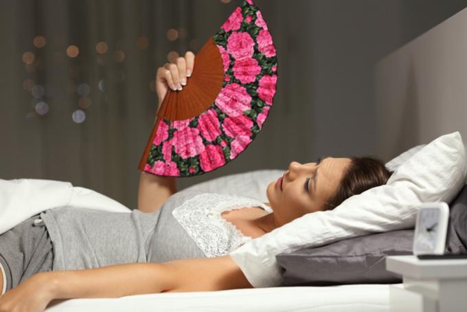 暑くて寝苦しそうな女性