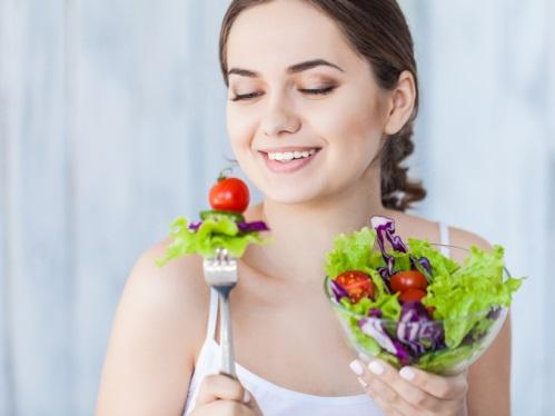 女性とサラダとお茶の写真