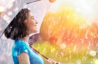 雨の中、傘をさし笑顔の女性