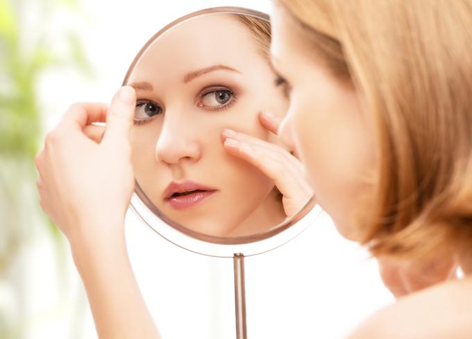 鏡で目元をチェックしている女性の画像