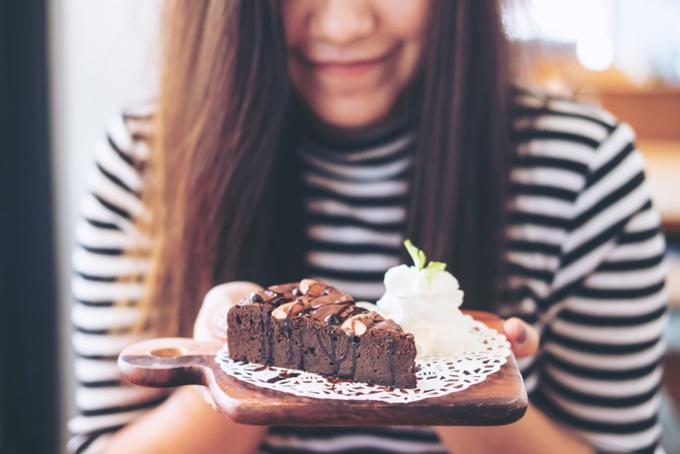 チョコレートケーキと生クリームを食べる女性