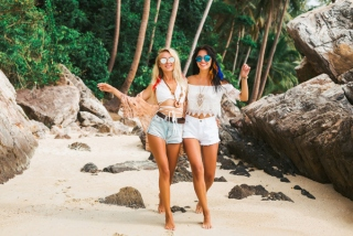 サングラスをかけて砂浜を歩く女性の画像