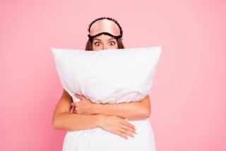 枕を抱えてピンクのアイマスクをつけた女性の画像