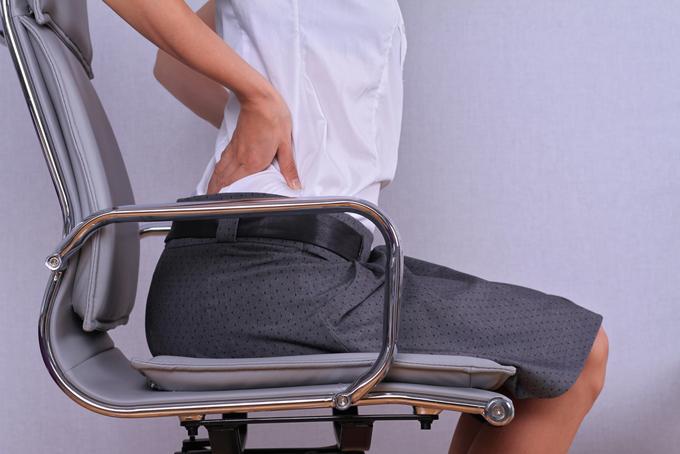 デスクワークで腰痛に悩む女性