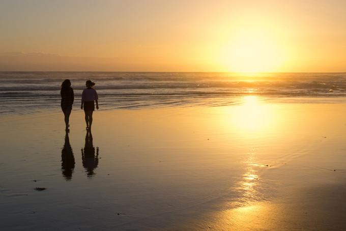 海辺をふたりの女性が歩く