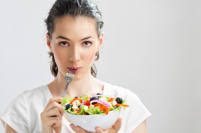不満足そうにサラダを口に運ぶ女性