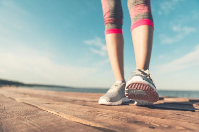 ウォーキングシューズを履いた女性の足元の画像