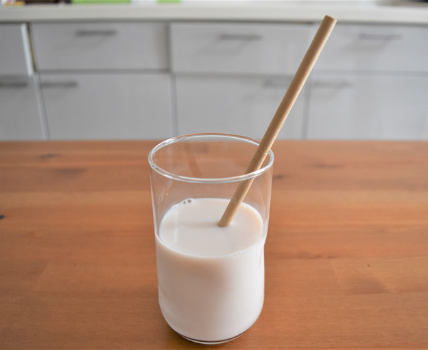 牛乳の入ったコップにさしたストローの画像