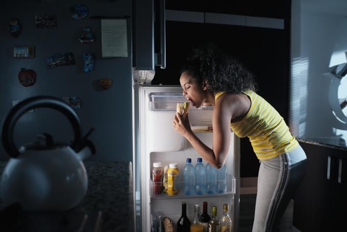 冷蔵庫のものを夜中に食べる女性