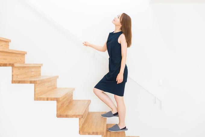 手すりを掴んで階段を上る女性の画像