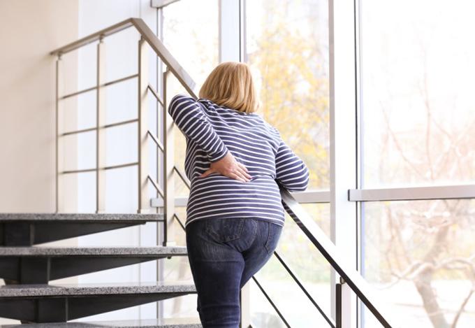重い体で階段をのぼる女性