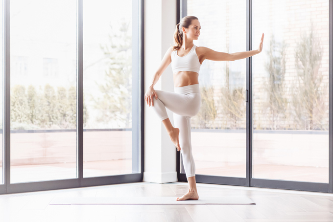 マットの上で片足バランスをとる女性の画像