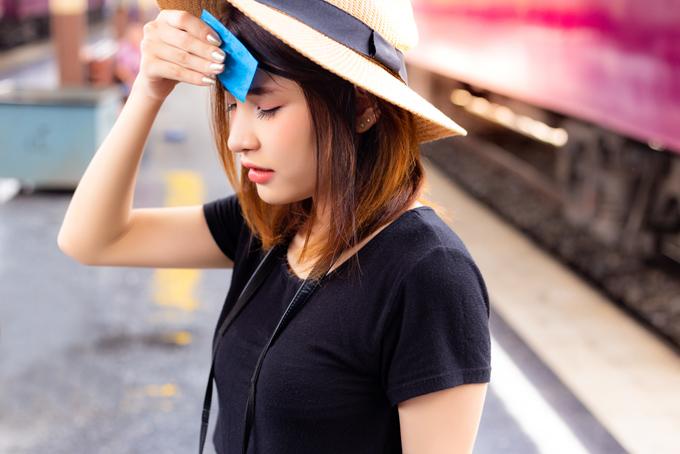 額の汗を押さえる女性の画像