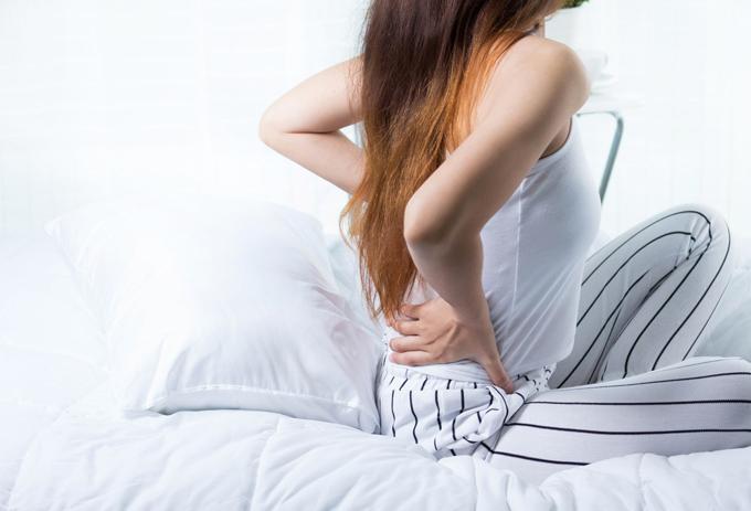 ベッドの上で腰を痛がる女性