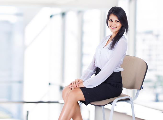 両手をそろえて椅子に座る女性の画像