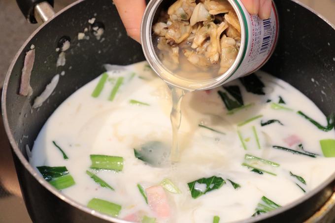 鍋で炒めてミルクとあさりの水煮汁をいれている写真