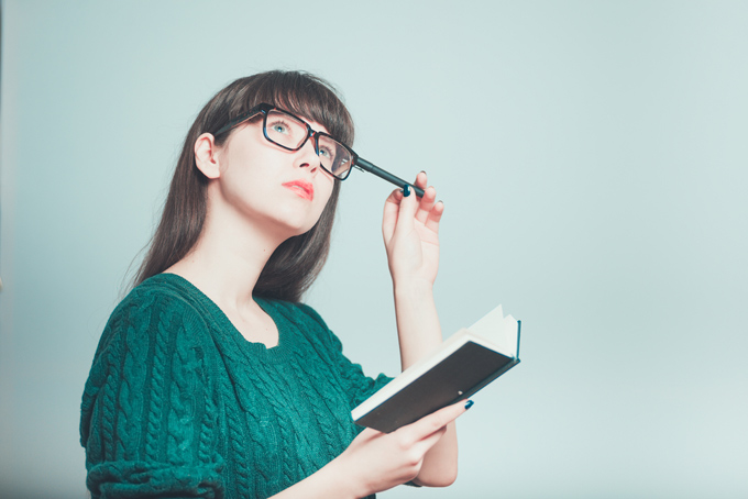ノートをペンを持って考えている女性のイメージ画像