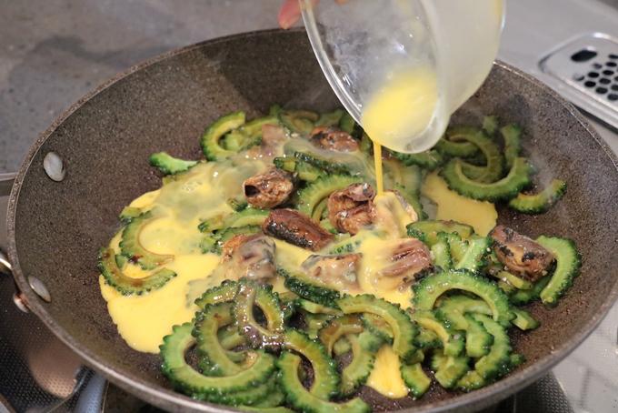ゴーヤといわしを炒め、溶き卵を回し入れている