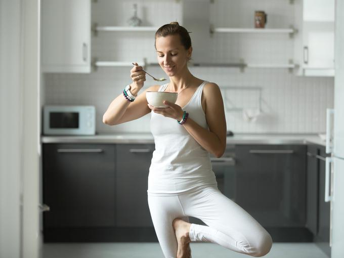 ヨガのポーズをしながら食事する女性