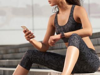 トレーニングの途中で階段に座って、スマホを見ている女性