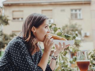 ホットドッグを頬張る女性の画像