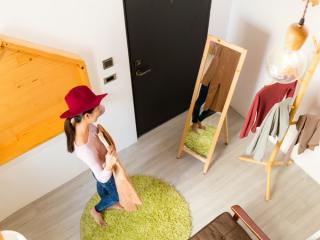 鏡の前で服を選んでいる女性の画像