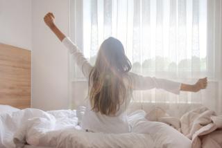 白いベッドの上でパジャマを着た寝起き女性の後ろ姿