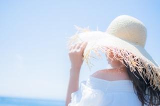 麦わら帽子をかぶり海辺にいる女性