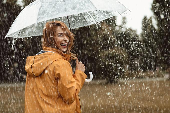雨の中傘をさす女性の画像