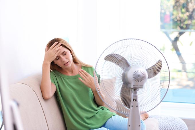 暑くて扇風機の前で休んでいる女性