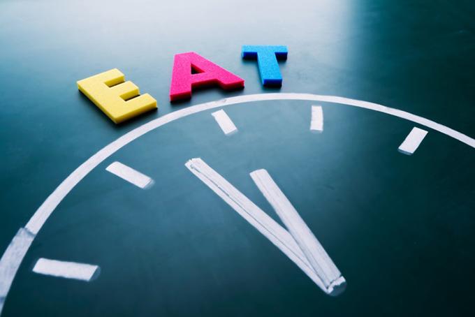 12時を指す時計の針と「EAT」の文字
