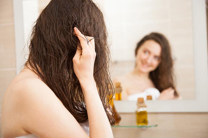 オイルでヘアケアしている女性の画像