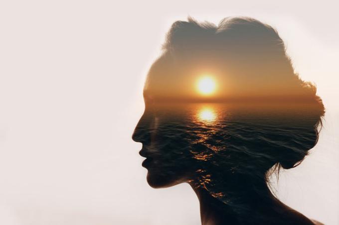 海と夕日を眺める女性