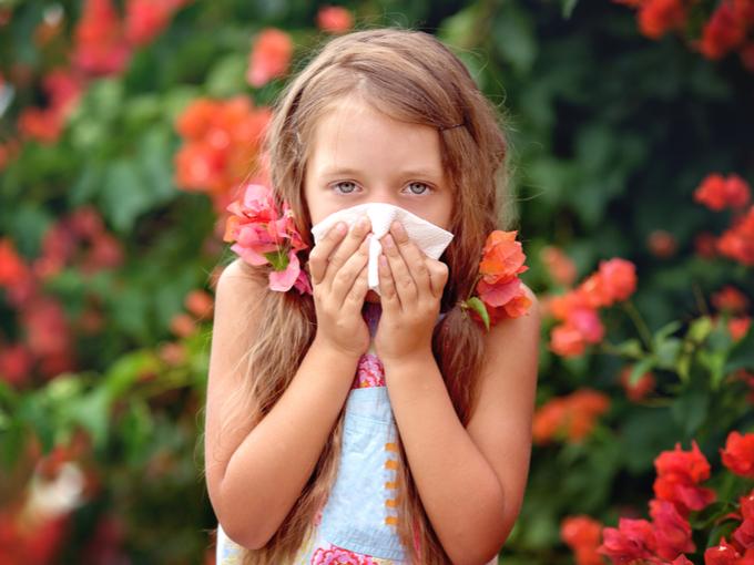 アレルギー性鼻炎で鼻をかむ少女