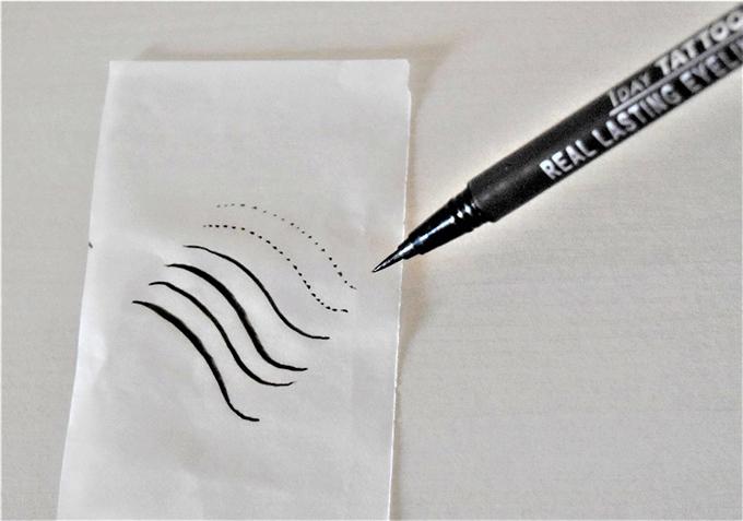 アイライナーと線の描かれた紙の画像