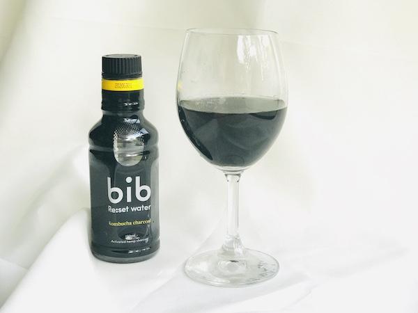 黒い飲料をグラスに注ぐ
