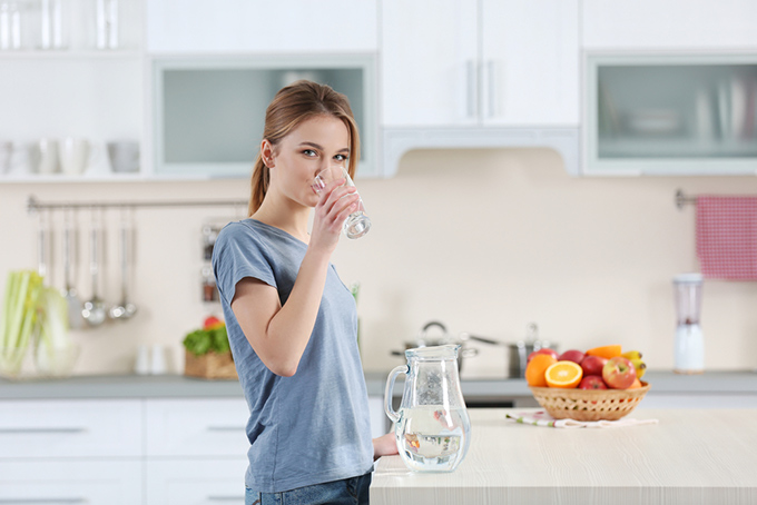 朝、水を飲んでいる女性の画像