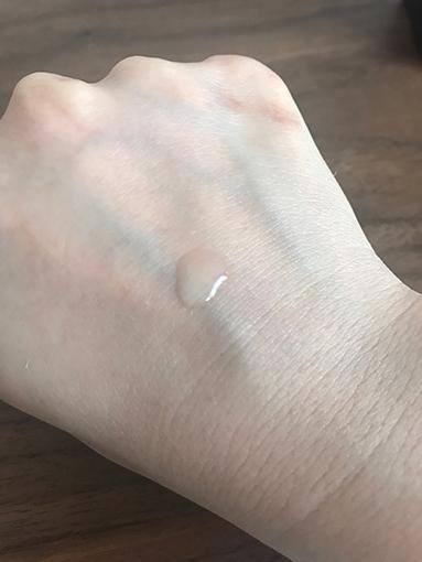 手の甲に化粧水を落とした(水滴が平たい)画像