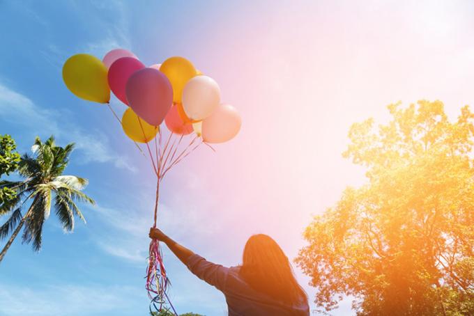 空に飛んでいく風船をつかむ