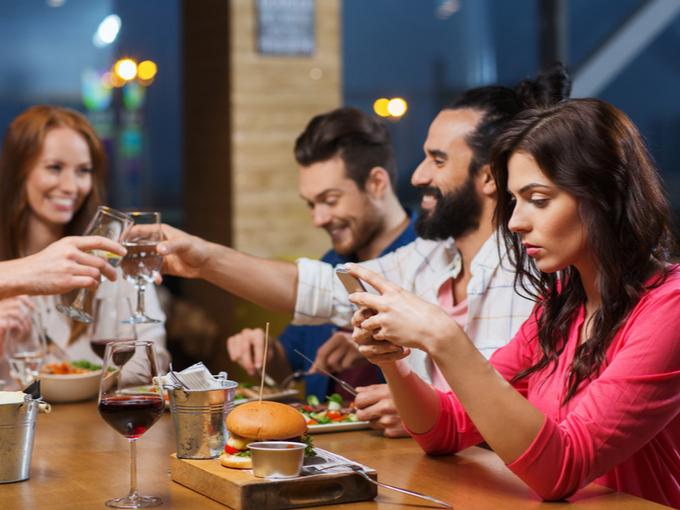 友人たちとの食事中でもSNSに没頭する女性