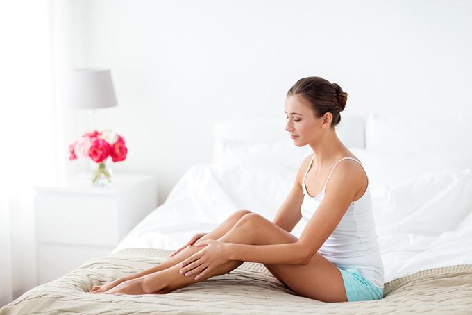 ベットの上で脚に触れている女性の画像