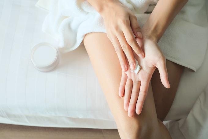 手にクリームを塗っている女性の画像
