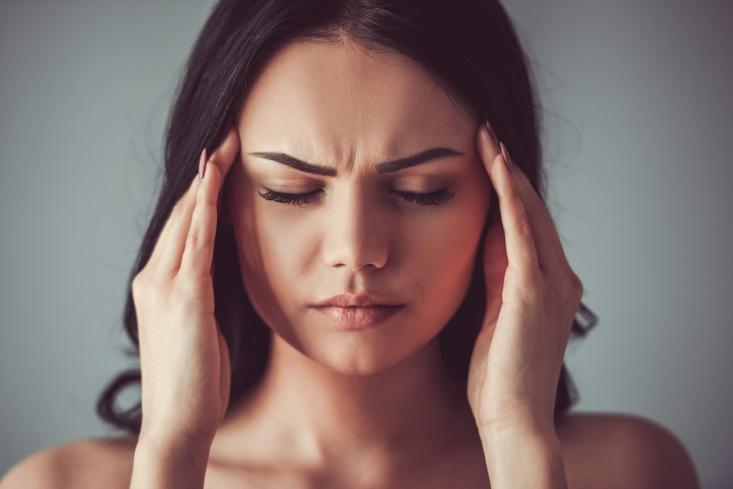 頭痛をつらそうにこめかみをおさえる女性