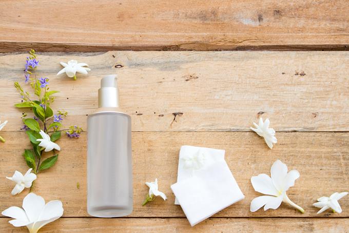 木の板に並んだスプレーボトルとコットンと花の画像