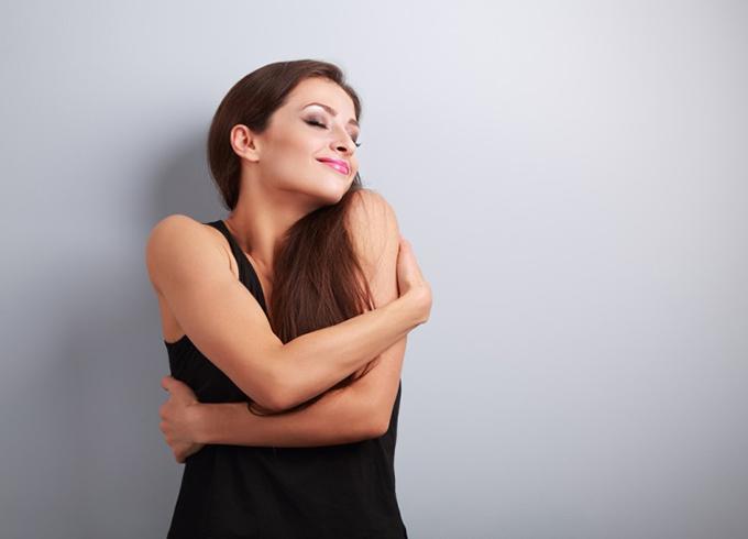 自分を大事に抱きしめる女性