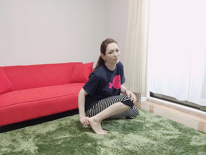 岡江さんが絨毯に座って自分のかかとに触れている画像